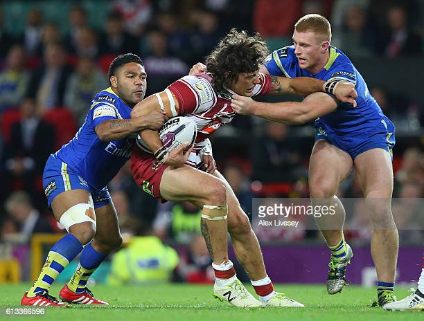 Anthony Gelling of Wigan Warriors is tackled by Jack Hughes of Warrington Wolves during the First Utility Super League Final between Warrington...