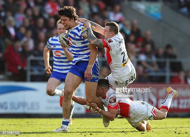 Anthony Gelling of Wigan Warriors is tackled by Jack Owens and Shannon McDonnell of St Helens during the First Utility Super League match between St...