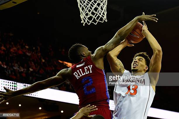 Anthony Gill of the Virginia Cavaliers drives to the basket against Tashombe Riley of the South Carolina State Bulldogs in the second half during a...