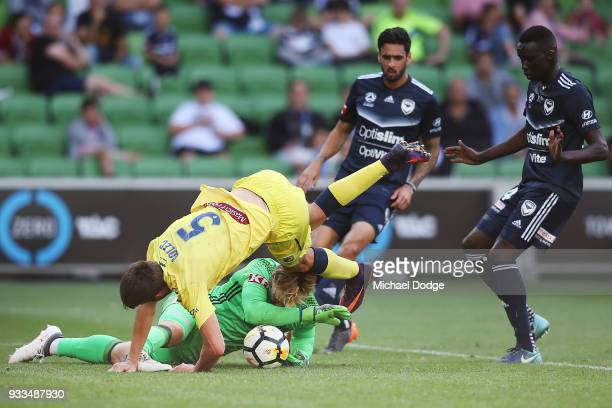 Anthony Golec of the Mariners crashes into Victory goalkeeper Lawrence Thomas in this contest and was later carried off on a stretcher with a leg...