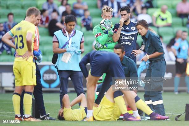 Anthony Golec of the Mariners reacts in pain after he crashes into Victory goalkeeper Lawrence Thomas in a contest and was later carried off on a...