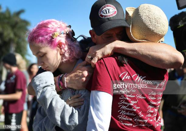 Anthony Gonzalez hugs his daughter Victoria Gonzalez and her teacher Ronit Reoven as they visit a memorial setup near Marjory Stoneman Douglas High...