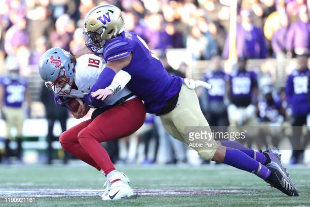 Anthony Gordon of the Washington State Cougars is sacked by Joe Tryon of the Washington Huskies in the third quarter during their game at Husky...