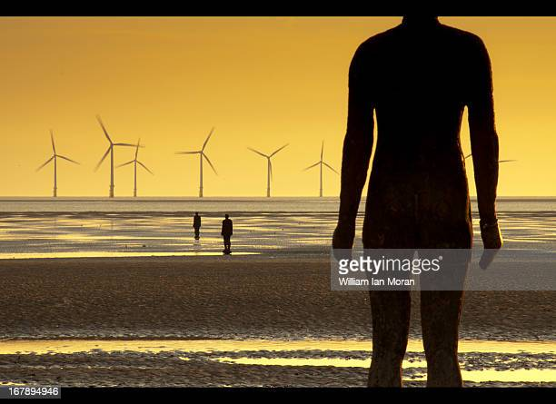 CONTENT] Anthony Gormley 'Another place' ironmen of Crosby beach on Merseyside with the wind farm at Burbo Bank as a backdrop Evening landscape sunset