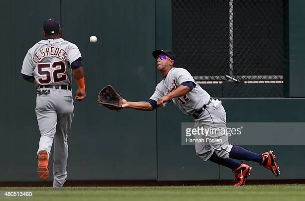 Anthony Gose of the Detroit Tigers makes a catch in center field of the ball off the bat of Joe Mauer of the Minnesota Twins as teammate Yoenis...