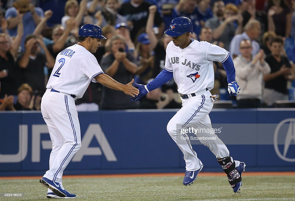 Anthony Gose #8 of the Toronto Blue Jays is congratulated by third base coach Luis Rivera #2 after hitting a solo home run in the fifth inning during MLB game action against the Baltimore Orioles on August 7, 2014 at Rogers Centre in Toronto, Ontario, Canada.
