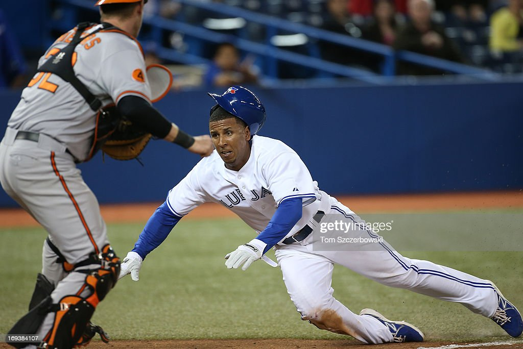 Anthony Gose #8 of the Toronto Blue Jays slides across home plate safely in the eighth inning during MLB game action as Matt Wieters #32 of the Baltimore Orioles looks to tag him on May 23, 2013 at Rogers Centre in Toronto, Ontario, Canada.