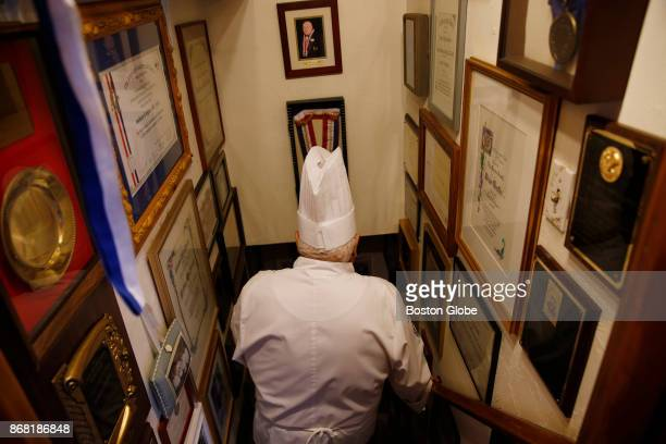 Anthony Graffeo walks downstairs passing his awards on the left and his wife Denise's awards on the right at their home in Saugus MA on Oct 24 2017...