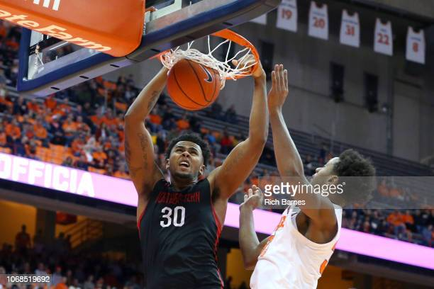 Anthony Green of the Northeastern Huskies dunks the ball as Elijah Hughes of the Syracuse Orange defends during the first half at the Carrier Dome on...