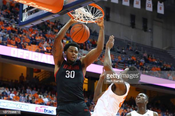 Anthony Green of the Northeastern Huskies dunks the ball as Elijah Hughes and Bourama Sidibe of the Syracuse Orange defend during the first half at...