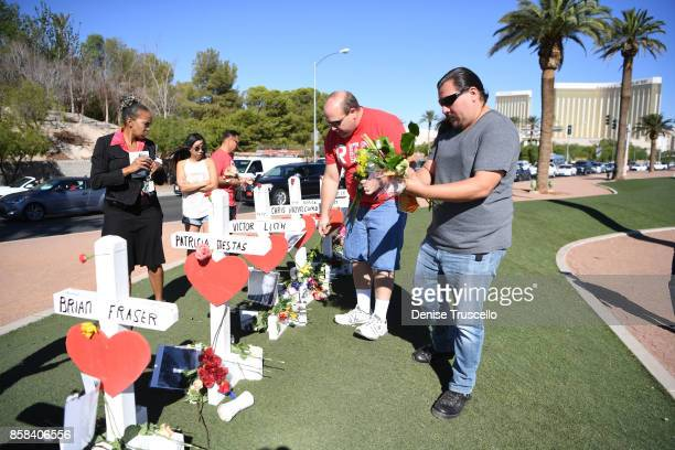 Anthony Guevara of Redlands California and Travis Johnson of Redlands California place flowers on crosses at the Welcome to Fabulous Las Vegas sign...