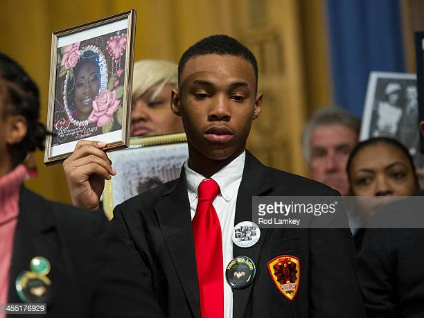Anthony Hardmon of Chicago Illinois holds a photo of his sister Ashley Hardmon who was shot and killed on July 2 2013 in Chicago as members of Faiths...