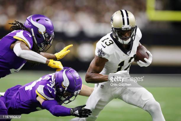 Anthony Harris and Andrew Sendejo of the Minnesota Vikings attempt to tackle Michael Thomas of the New Orleans Saints during the first half in the...