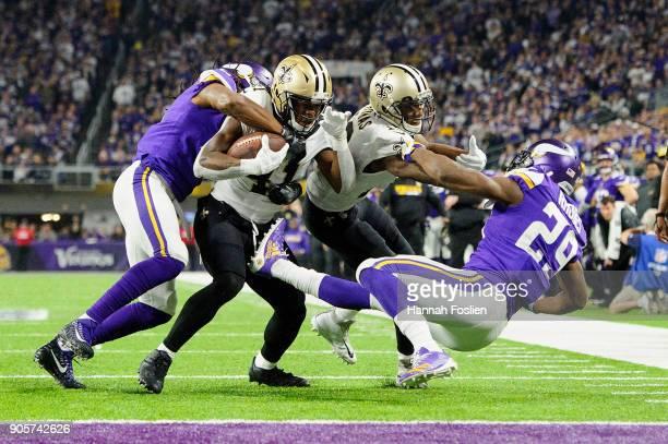 Anthony Harris of the Minnesota Vikings tackles Alvin Kamara of the New Orleans Saints as Michael Thomas of the New Orleans Saints blocks Xavier...