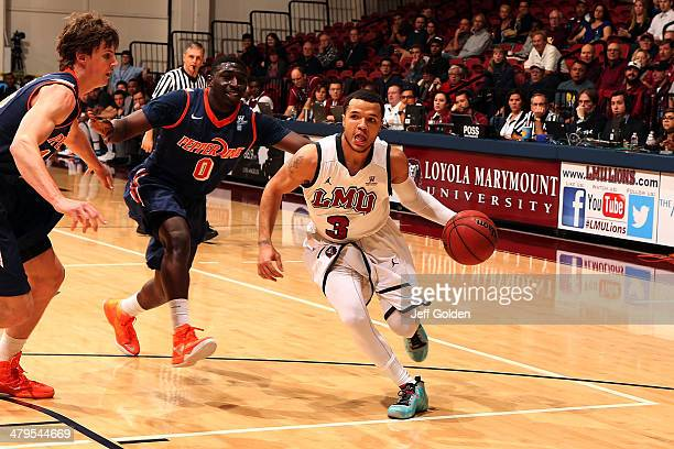 Anthony Ireland of the Loyola Marymount Lions drives against Amadi Udenyi and Jett Raines of the Pepperdine Waves in the first half of the game at...