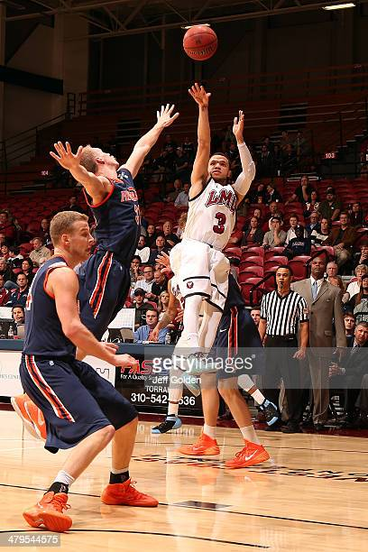 Anthony Ireland of the Loyola Marymount Lions shoots a jump shot while airborne against Nikolas Skouen and Malte Kramer of the Pepperdine Waves in...