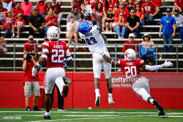 Anthony Johnson of the Buffalo Bulls catches a pass as Avery Young of the Rutgers Scarlet Knights defends and Damon Hayes of the Rutgers Scarlet...