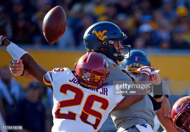 Anthony Johnson of the Iowa State Cyclones forces a fumble in the first half against Austin Kendall of the West Virginia Mountaineers at Mountaineer...