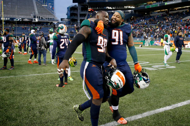 Anthony Johnson of the Seattle Dragons right hugging teammate Kenneth Farrow as they left the field after defeating the Tampa Bay Vipers at...