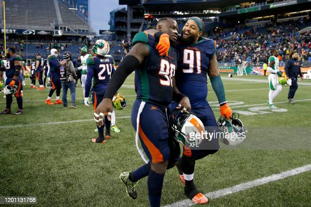 Anthony Johnson of the Seattle Dragons, right, hugging teammate, Kenneth Farrow, as they left the field after defeating the Tampa Bay Vipers at...