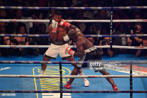 Anthony Joshua and Carlos Takam in action during their IBF, WBA & IBO Heavyweight Championship contest at Principality Stadium on October 28, 2017 in...