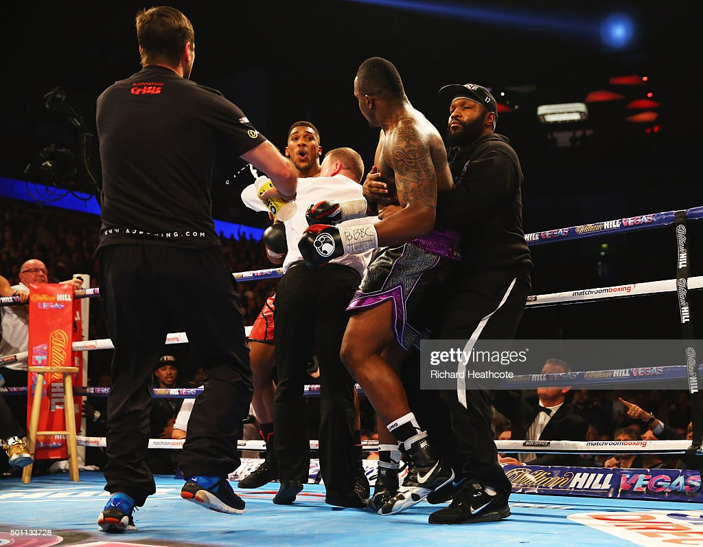 Anthony Joshua and Dillian Whyte are pulled apart as they exchange punches after the bell at the end of the first rouns during the British and Commonwealth heavyweight title contest at The O2 Arena on December 12, 2015 in London, England.