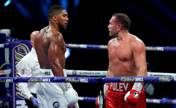 Anthony Joshua and Kubrat Pulev stare at each other as they walk to the corners in between rounds at The SSE Arena, Wembley on December 12, 2020 in...