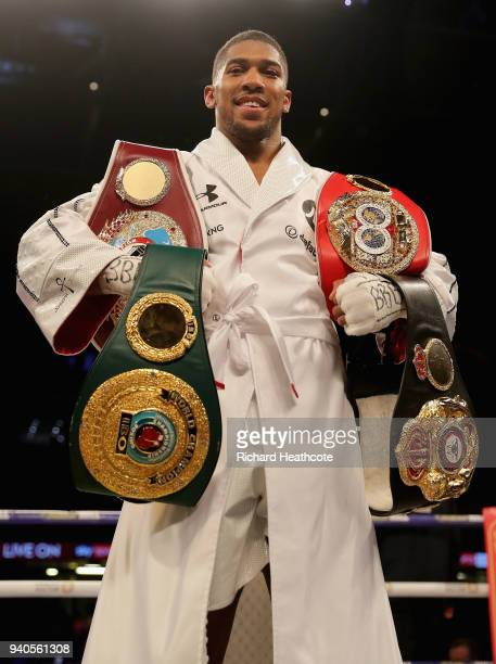 Anthony Joshua celebrates poses with his belts after his WBA IBF WBO IBO Heavyweight Championship title fight against Joseph Parker at Principality...