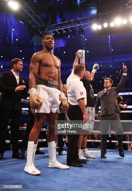 Anthony Joshua cuts a dejected figure as Oleksandr Usyk celebrates after being crowned the new World Champion following the Heavyweight Title Fight...