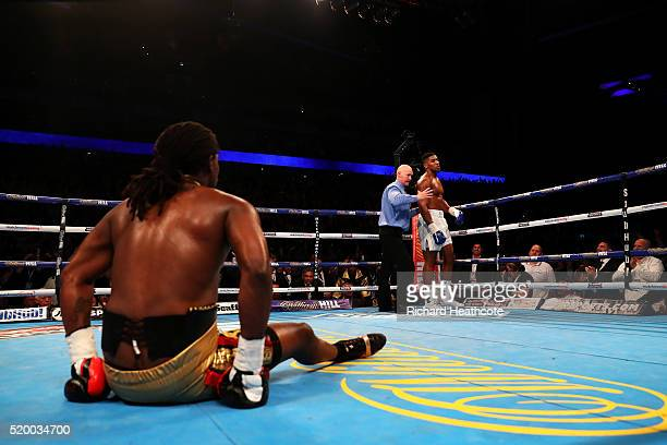 Anthony Joshua of England is ordered back to his corner by the referee as Charles Martin of the United States sits on the canvas during the IBF World...