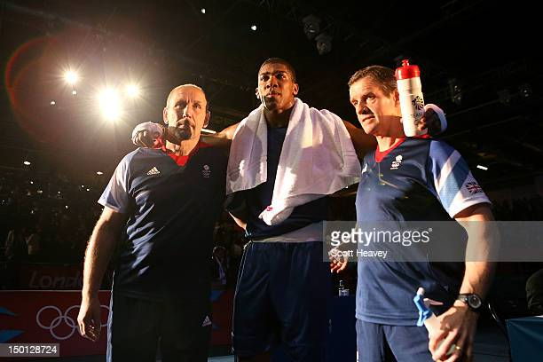Anthony Joshua of Great Britain poses with his corner men after he was declared the winner against Ivan Dychko of Kazakhstan during their Men's Super...