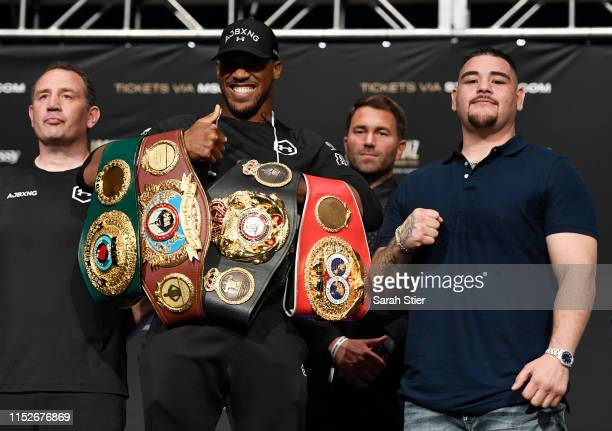 Anthony Joshua of the United Kingdom holds his belts while posing with Andy Ruiz of Mexico during the press conference prior to their world...