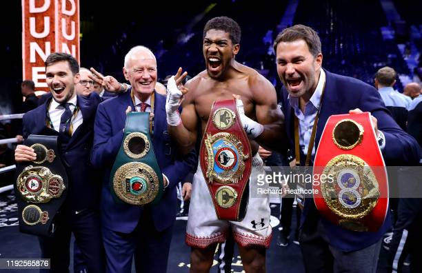 Anthony Joshua poses for a photo with the IBF, WBA, WBO & IBO World Heavyweight Title belts with Eddie Hearn and Barry Hearn after the IBF, WBA, WBO...