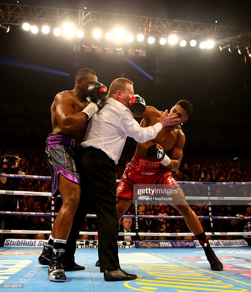 Anthony Joshua (R) throws a punch after the bell at the end of the first round as the referee intervenes during the British and Commonwealth heavyweight title contest against Dillian Whyte (L) at the Matchroom Boxing promotion 'Bad Intentions' at The O2 Arena on December 12, 2015 in London, England.