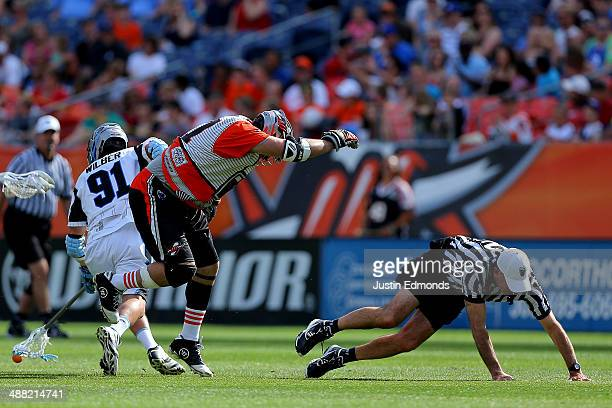 Anthony Kelly of the Denver Outlaws knocks the referee to the ground after losing a battle for a ground ball with Dana Wilber of the Ohio Machine at...