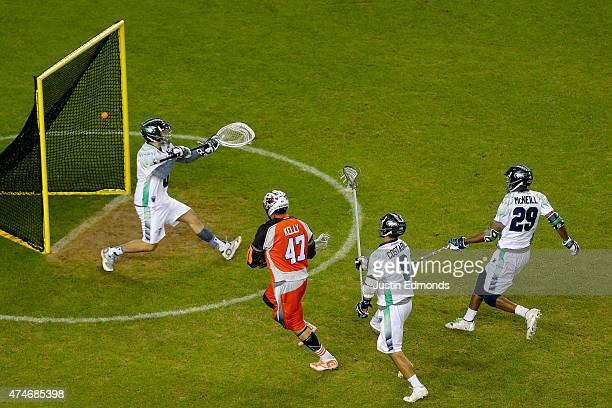 Anthony Kelly of the Denver Outlaws scores a thirdquarter goal past Tyler Fiorito of the Chesapeake Bayhawks as CJ Costabile and Mark McNeill of the...