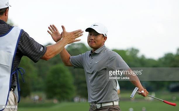 Anthony Kim celebrates with his caddie after winning the Wachovia Championship at Quail Hollow Country Club on May 4 2008 in Charlotte North Carolina