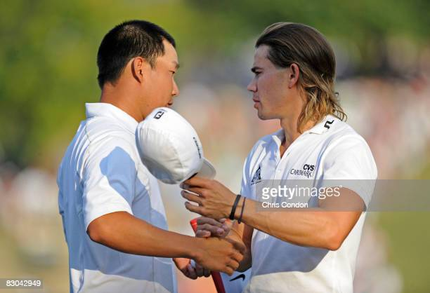 Anthony Kim shakes hands with Camilo Villegas of Colombia on the 18th green during the final round of THE TOUR Championship presented by CocaCola at...