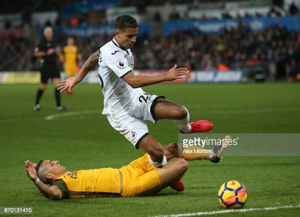 Anthony Knockaert of Brighton and Hove Albion falls down with Kyle Naughton of Swansea City during the Premier League match between Swansea City and...