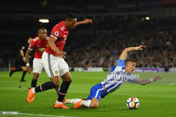 Anthony Knockaert of Brighton Hove Albion goes down in the box as he is challenged by Anthony Martial of Manchester United during the Premier League...