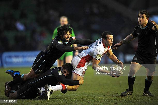 Anthony Laffranchi of St Helens passes the ball on as Chad Randell and Julien Rinaldi of Broncos come in to tackle him during the Stobart Super...