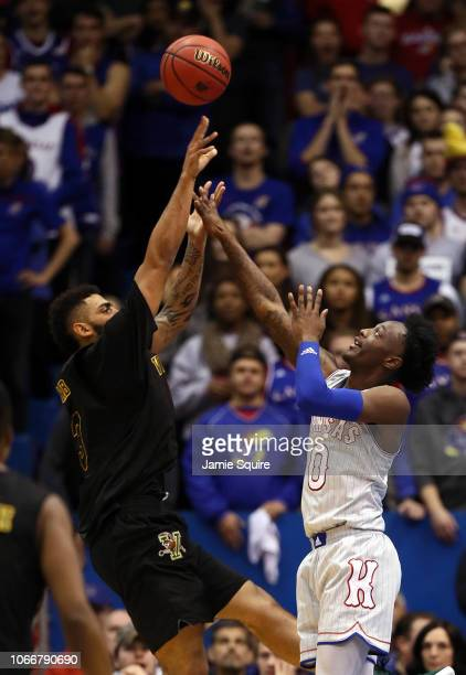 Anthony Lamb of the Vermont Catamounts shoots over Marcus Garrett of the Kansas Jayhawks during the game at Allen Fieldhouse on November 12 2018 in...