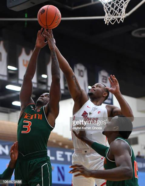 Anthony Lawrence II of the Miami Hurricanes and Christian Gray of the Fresno State Bulldogs reach for a rebound in the second half of the game in the...