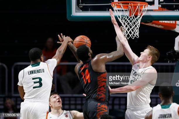 Anthony Lawrence II of the Miami Hurricanes blocks a shot by Elijah Thomas of the Clemson Tigers during the second half at the Watsco Center on...