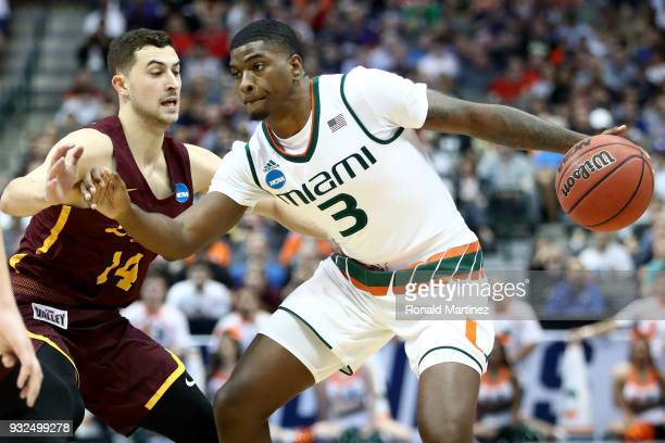 Anthony Lawrence II of the Miami Hurricanes drives on Ben Richardson of the Loyola Ramblers in the first half in the first round of the 2018 NCAA...