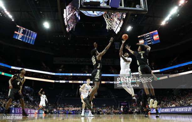 Anthony Lawrence II of the Miami Hurricanes drives to the basket against teammates Jaylen Hoard and Isaiah Mucius of the Wake Forest Demon Deacons...