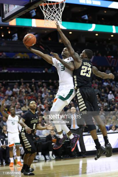 Anthony Lawrence II of the Miami Hurricanes drives to the basket against Chaundee Brown of the Wake Forest Demon Deacons during their game in the...