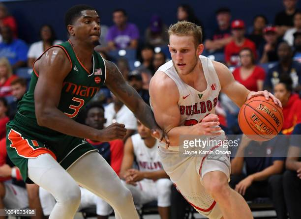 Anthony Lawrence II of the Miami Hurricanes guards Sam Bittner of the Fresno State Bulldogs as he takes the ball along the baseline in the second...