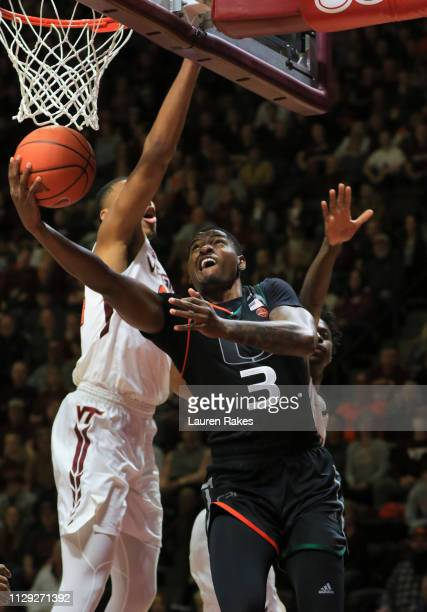 Anthony Lawrence of the Miami Hurricanes shoots past Kerry Blackshear Jr #24 of the Virginia Tech Hokies in the first half at Cassell Coliseum on...