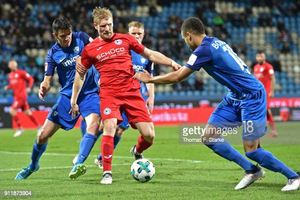 Anthony Losilla and Jan Gyamerah of Bochum tackle Andreas Voglsammer of Bielefeld during the Second Bundesliga match between VfL Bochum 1848 and DSC...